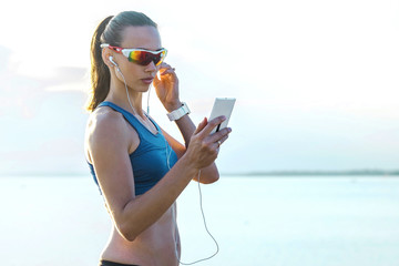 Running woman in sport sunglasses. Female runner with her smartp