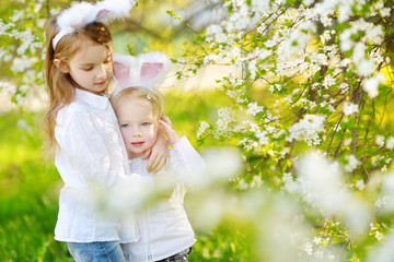 Two adorable little sisters wearing bunny ears in a spring garden on Easter day