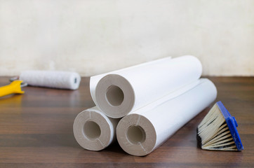 wallpaper rolls and brush on the floor for home repair