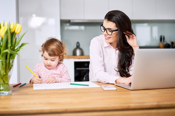 Mother working from home and taking care of her child