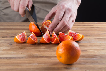 Blood oranges , cut into slices on a cutting board. Concept.