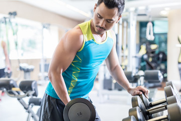Portrait of a handsome and determined Middle-Eastern young man exercising bicep curls with a heavy dumbbell during upper-body workout routine