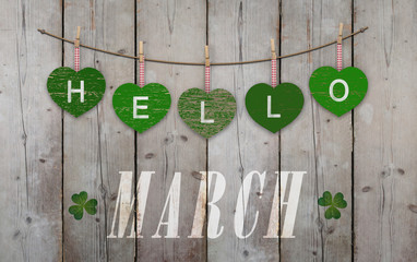 Hello March written on hanging green hearts and weathered wooden background, with clover