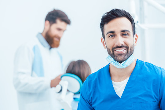 Portrait of a confident dental surgeon wearing blue protective uniform and surgical mask while looking at camera in a modern dental office with reliable specialists