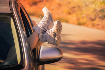 Female legs on the vehicle door through open window in the boots