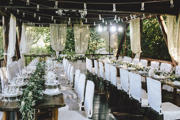 Decorated elegant wooden wedding table for banquet outdoor in garden gazebo with lamp, in the style of rustic with eucalyptus and flowers, porcelain plates, glasses, white chairs