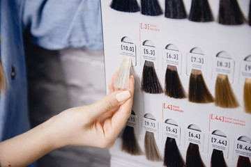 Hairdresser holds palm hair color palette against white brick wall. Hair coloring in salon