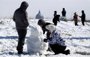 Saint Peter's Basilica is seen in the background as people enjoy the snow following a heavy snowfall at the Circus Maximus in Rome