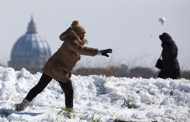 A woman throws a snowball as Saint Peter's Basilica dome is seen in the background after a heavy snowfall in Rome