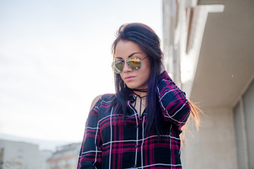 Stylish young brunette woman in sunglasses posing