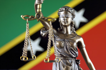 Symbol of law and justice with Saint Kitts and Nevis Flag. Close up.