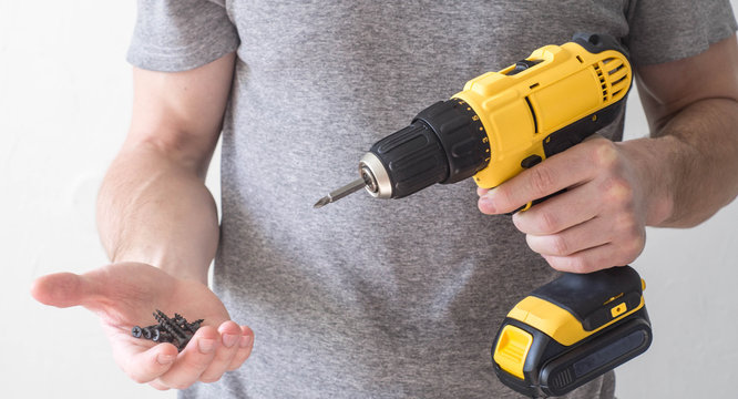 Hand electric tool: a yellow electric screwdriver in the hands of a man and a screw in the palm