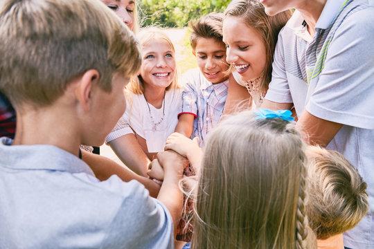 Happy children team heaping hands in summer