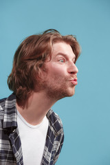 Portrait of attractive cute man with kiss isolated over blue background