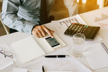 Finger businessman using smartphone with analysis summary chart on desk.