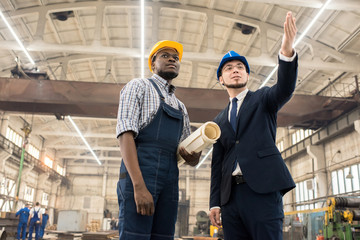 Confident inspector in classical suit pointing at something while young technician with blueprint in hands giving tour of modern factory, interior of spacious production department on background