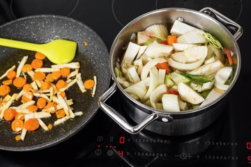 Boiling of vegetable soup in pot on cooker.
