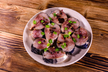 Sliced scomber fish with green onion on a ceramic plate on wooden table