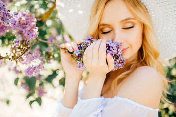 Young cute pretty blonde amazing model girl in white dress portrait in park outdoor. Beautiful happy girl with expressive face in blooming lilac garden. Spring is coming. Branches and trees. Easiness.