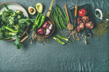 Winter vegetarian, vegan food cooking ingredients. Flat-lay of vegetables, fruit, beans, cereals, kitchen utencil, dried flowers, olive oil over grey linen table cloth background, top view, copy space