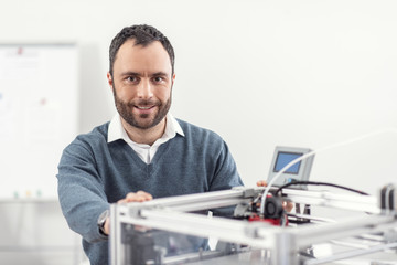State-of-the-art technology. Charming upbeat young man posing for the camera while standing near a 3D printer and touching its body