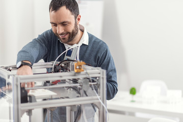 Thorough preparation. Pleasant young man setting up a 3D printer, checking its progress and touching a ready part of the 3D model while smiling