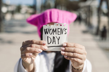 woman with a pink hat and the text womens day