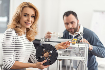 True professional. Pretty young woman posing for the camera while holding a filament spool connected to the 3D printer while her colleague holding a half-printed model