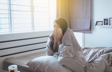 Young asian woman coughing and sitting on her bed,Concept of health