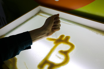 Woman's hand is drawing bitcoin with sand on the glass lighted surface. Financial growth cryptocurrency. Art and business. Original image of virtual cash sign.