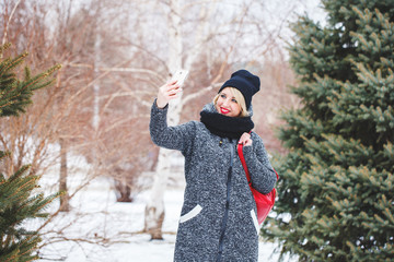 A beautiful hipster girl in a gray coat and a black hat makes selfie on the phone outdoors. Portrait of a modern girl who makes selfie, space for text.