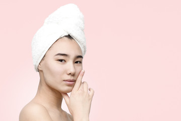 Close up portrait of pretty young asian woman with clean fresh skin after shower with towel on head on the rose background. Beauty, skincare, lifestyle concept