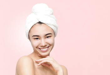 Indoor portrait of cheerful smiling attractive asian woman holding white towel on head wrapped in yellow towel isolated on the rose background. Beauty, skincare, lifestyle concept