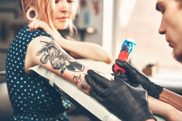 Young beautiful girl looks like the tattoo artist does the tattoo, reading the news in the smartphone