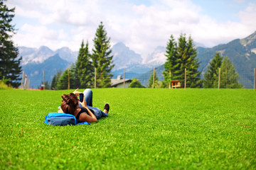 woman tourist resting on green lawn and taking pictures on phone alpine meadows and mountains