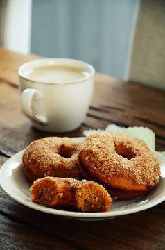 Cup of coffee with pumpkin spice whole wheat doughnuts on wooden table