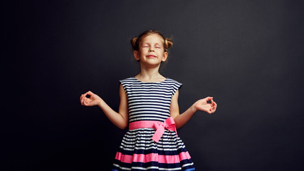 Peaceful girl meditating and relaxing over studio background. Concept of  childhood and development.
