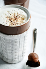 Large mug of latte macchiato with knitted mug protector to keep coffee warm and protect hands. Chocolate truffle candy on spoon, white background.