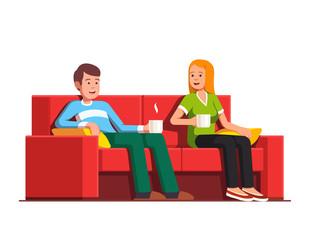 Husband and wife siting on sofa drinking tea