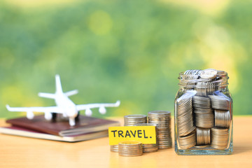 Saving planning for Travel budget of holiday concept,Financial,Stack of coins money in the glass bottle and airplane on passport with natural green background