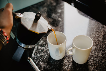 Preparing fresh coffee in moka pot on electric stove. Pouring hot steaming coffee into two white mugs.