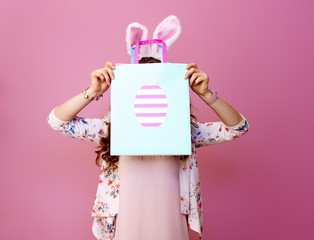 young woman on pink background hide behind Easter shopping bag