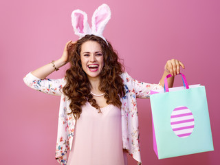 woman isolated on pink background with Easter shopping bag