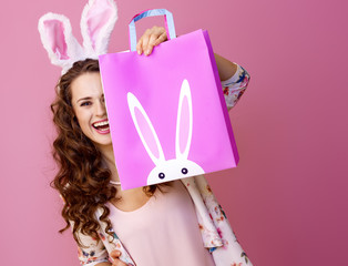 happy woman isolated on pink hiding behind Easter shopping bag