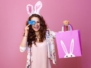 woman isolated on pink with Easter shopping bag and credit card