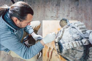 Restaurator arbeitet an einem historischem Stück zur Erhaltung