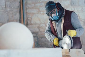Steinmetz arbeitet mit Schutzkleidung in der Werkstatt