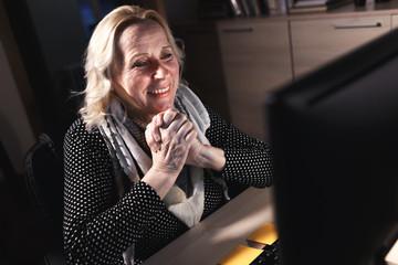 Smiling mature businesswoman working on desktop at night.