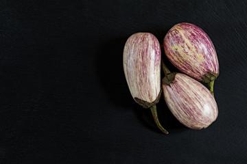 Purple graffiti three eggplants on black stone surface. Top view, copy space.