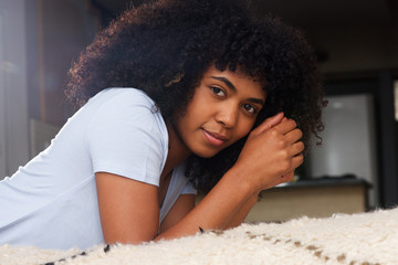 Close up beautiful african young woman lying on floor in living room